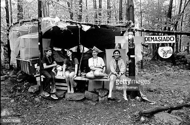Four young people sit in a handmade tent in the woods at the Woodstock Music Art Fair Bethel NY August 15 1969