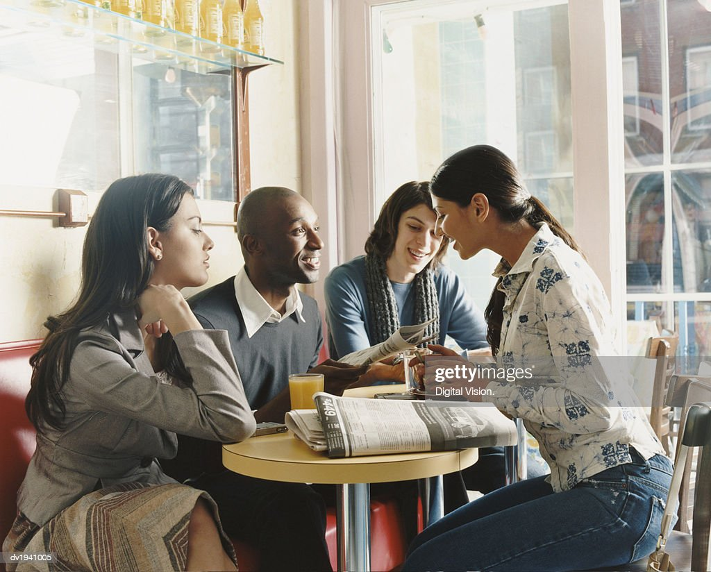 Four Young People Sitting in a Cafe : Stock Photo