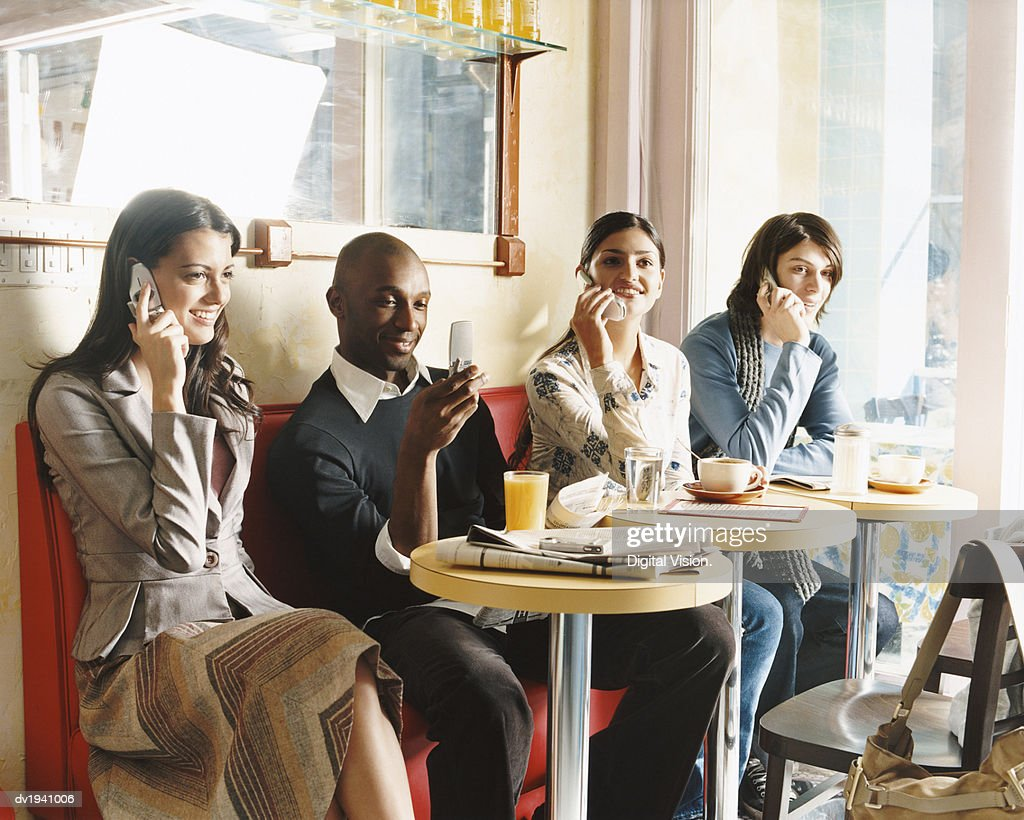 Four Young People Sitting in a Cafe Using Mobile Phones : Stock Photo