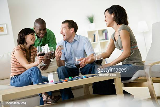 four young people sitting in living room at home, drinking wine, laughing and playing board game - game board stock photos and pictures