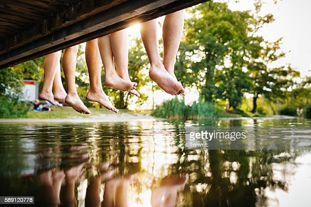 four young people sitting on a jetty - serene people stock pictures, royalty-free photos & images