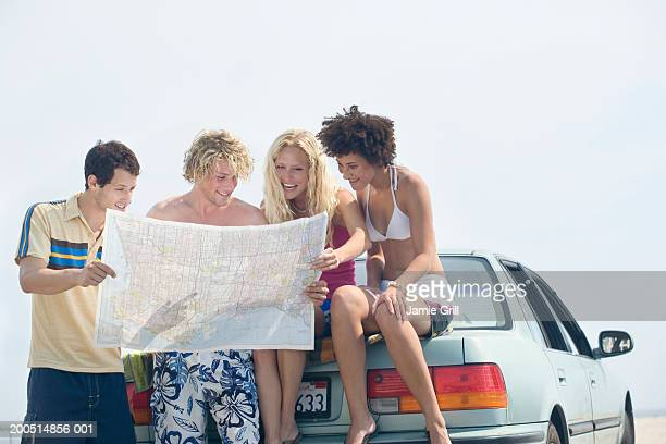 Four young people sitting on car trunk reading map