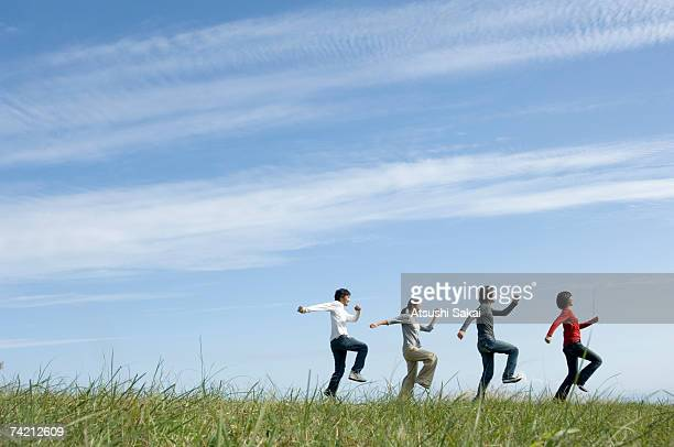 Four young people skipping in field