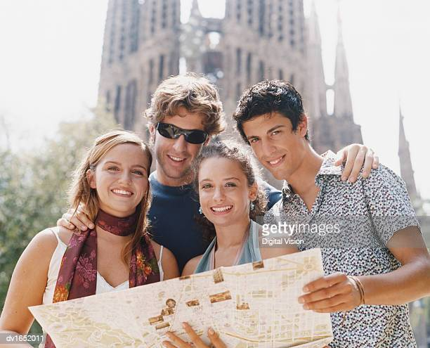 Four Young People Stand Holding a Map in Front of the Sagrada Familia, Barcelona