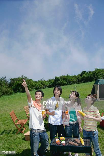 Four young people standing behind of barbecue grill