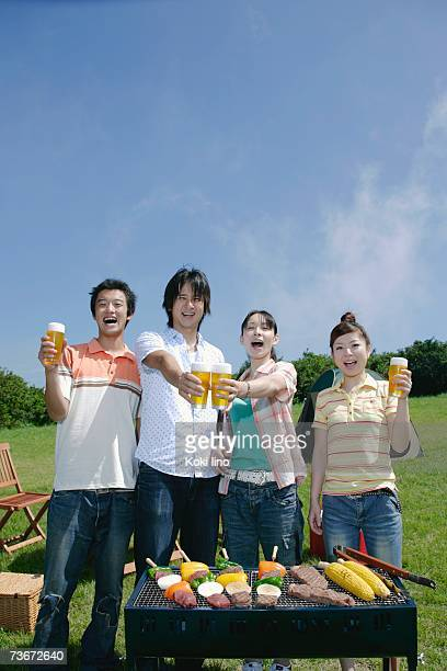 Four young people toasting with beer