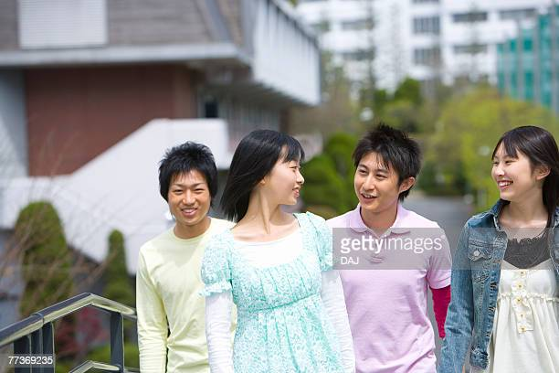 Four young people walking on footbridge, smiling, front view, Japan