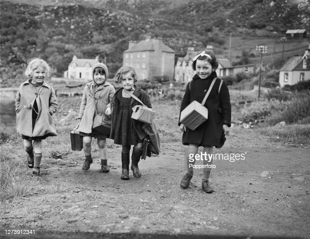 Four young schoolgirls carry their gas masks in boxes while walking home from school in the town of Mallaig on the west coast of the Highlands of...