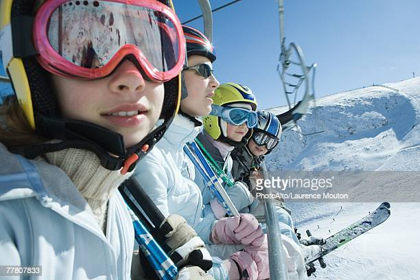 Four young skiers on chair lift, two looking at camera