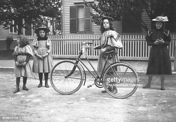 Four young smartly dressed girls standing outside the front of a house, one holding a bicycle with a ribbon tied around the handlebars. Boston...