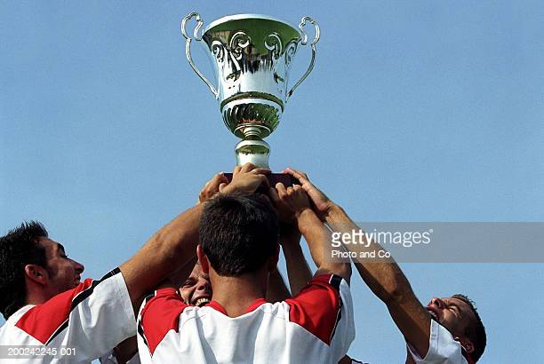 Four young sportsmen, holding up trophy outdoors, close-up