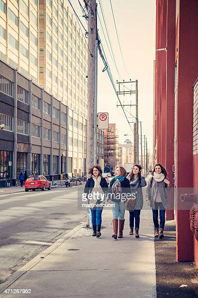 """four young urban women walking on a city street. - """"martine doucet"""" or martinedoucet stock pictures, royalty-free photos & images"""
