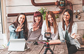 four young vloggers talking camera leaning