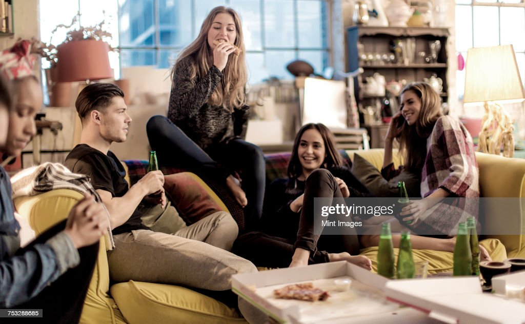 Four young women and young man sitting on a sofa, smiling, pizza and beer bottles on coffee table. : Stock Photo