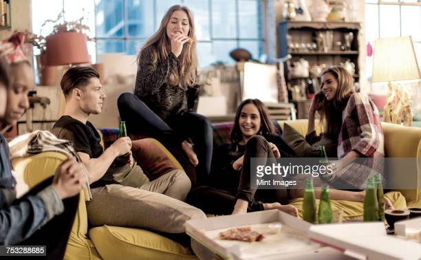 Four young women and young man sitting on a sofa, smiling, pizza and beer bottles on coffee table.
