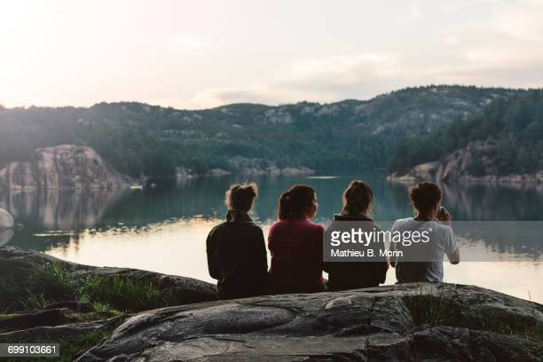 four young women are sitting and relaxing by the lake at dusk - sudbury canada stock photos and pictures