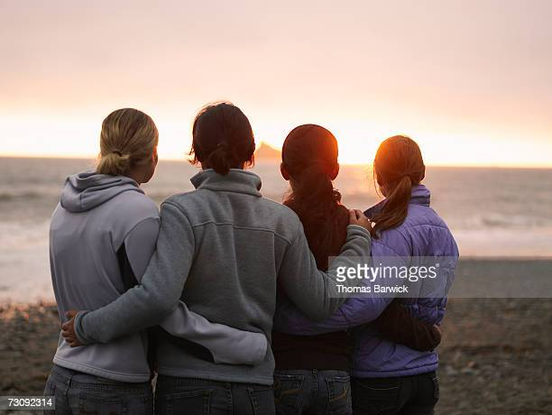 four young women, arms around each other, looking out to sea, rear view - arm around stock pictures, royalty-free photos & images
