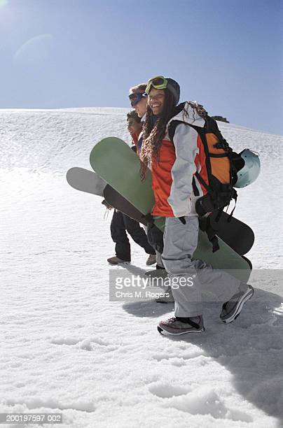 Four young women carrying snowboards, side view