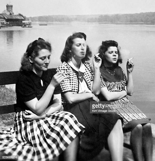 Four young women enjoy their cigarettes on a lakeside bench