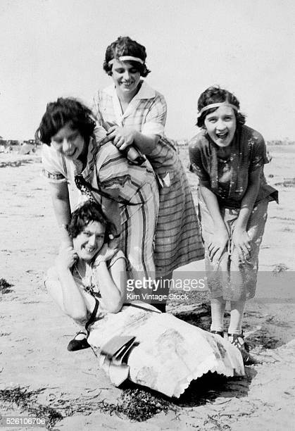 Four young women frolic and laugh on a beach ca 1920