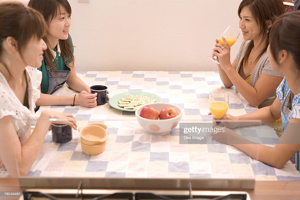 Four young women gathered at the table : Stock Photo