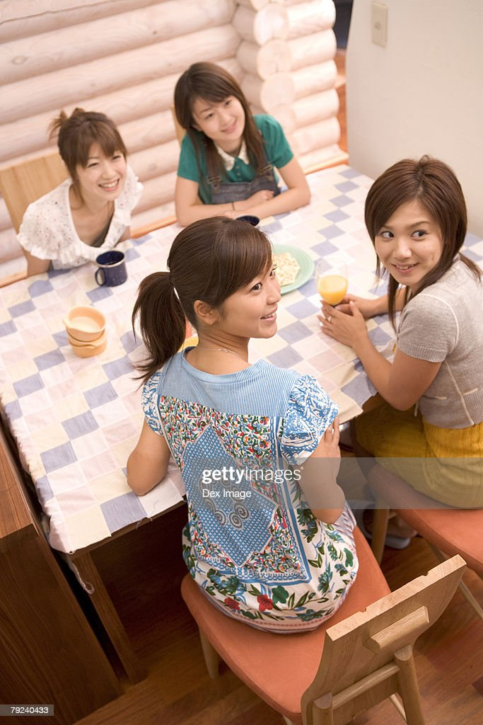 Four young women gathered at the table, top view : Stock Photo