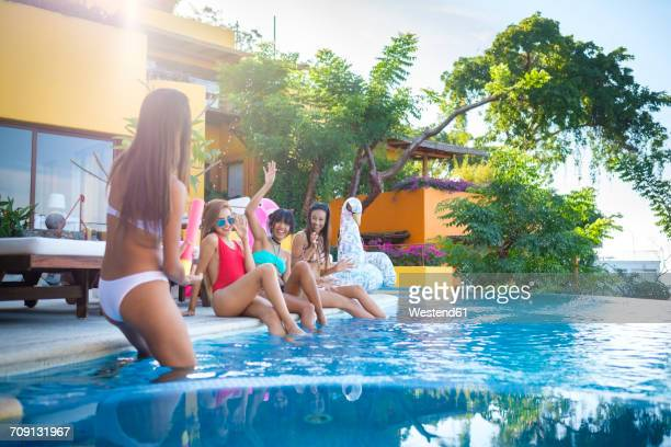 Four young women having fun at the poolside