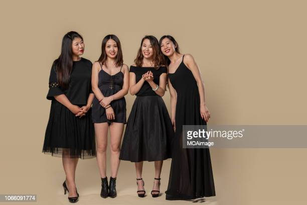 four young women in black dress - beige background stock pictures, royalty-free photos & images