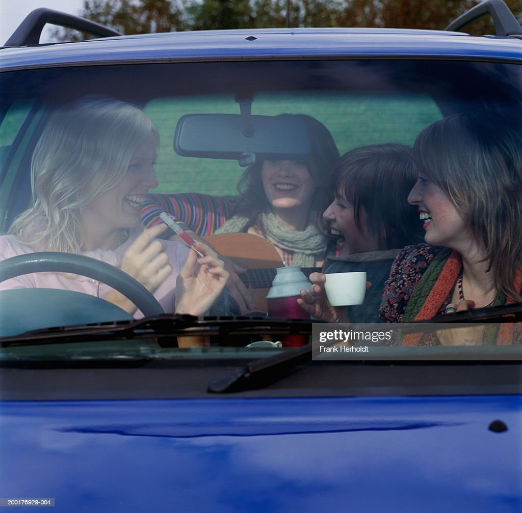 Four young women in car, laughing, view through front window : Stock Photo
