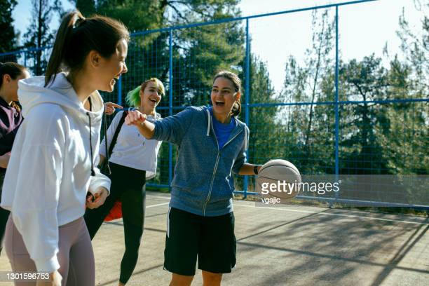 four young women on the court ready to play basketball - basketball sport stock pictures, royalty-free photos & images