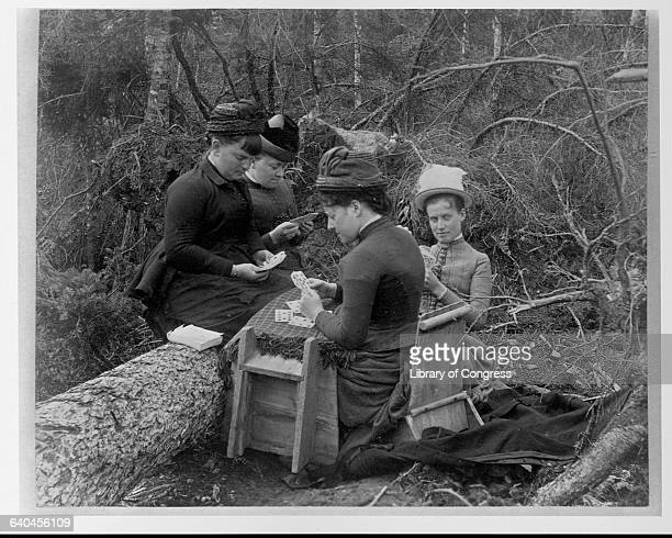 Four young women play cards on a makeshift table in the forest near the first falls of Maine's Socateau River | Location first falls of Socateau...
