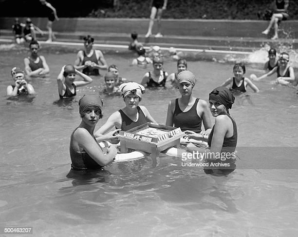 Four young women playing MahJong on a floating table in a swimming pool Washington DC June 20 1924
