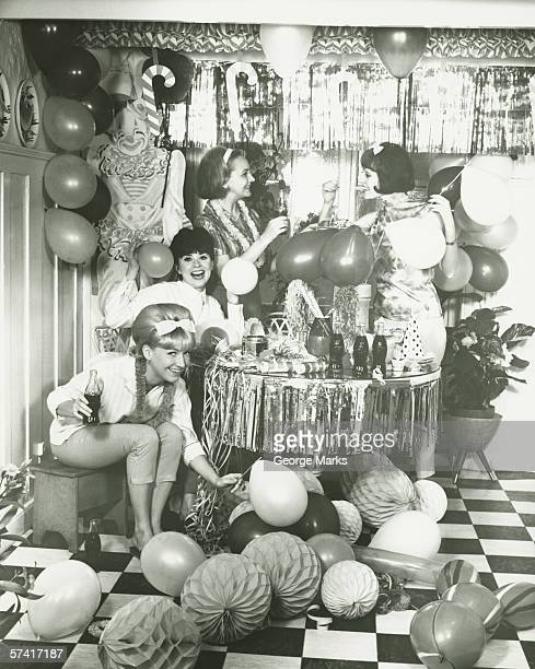 Four young women preparing decorations for party , (B&W)