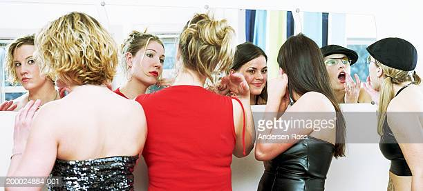 four  young women putting on makeup in mirror, high section, rear view - clubkleding stockfoto's en -beelden