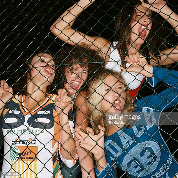 Four Young Women Screaming Behind Fence