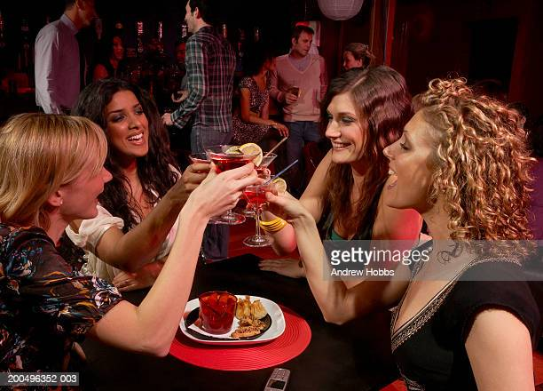 Four young women sitting in bar with cocktails, making toast, smiling
