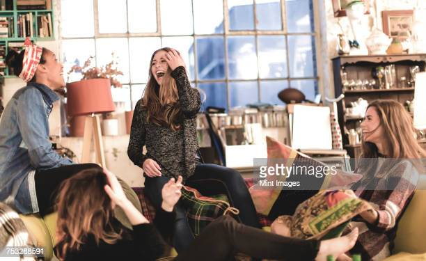 four young women sitting indoors on a sofa, laughing. - vier personen stockfoto's en -beelden