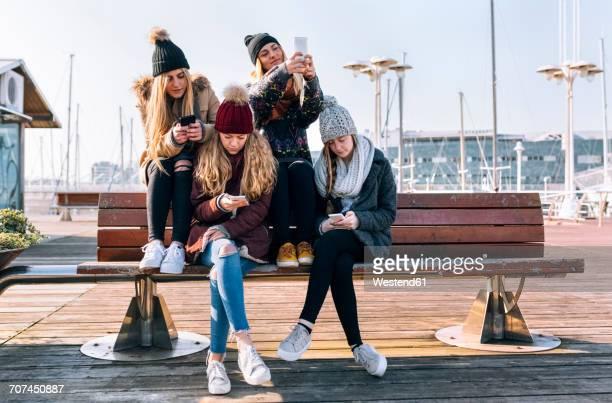 four young women sitting on a bench using their cell phones - quatre personnes photos et images de collection