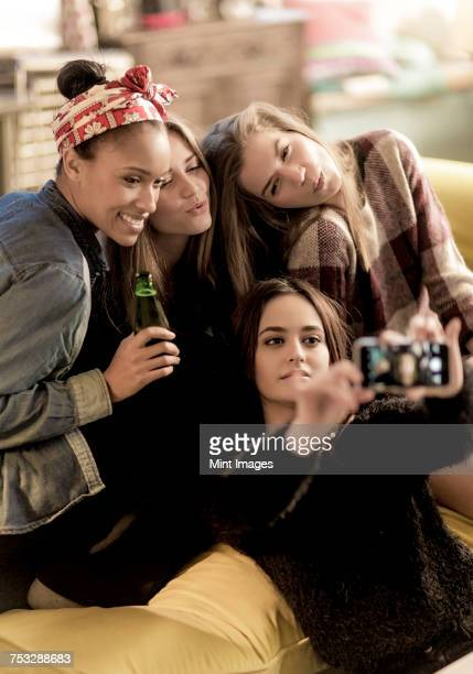 Four young women sitting on a sofa, smiling, taking a selfie, holding beer bottles.