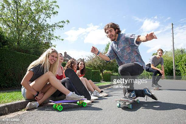 four young women sitting on kerb watching skateboarders - アマシャム ストックフォトと画像