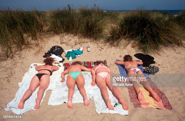 Four young women sunbathe in their bikinis in coastal dunes on 25th May 1992 in Great Yarmouth Suffolk England
