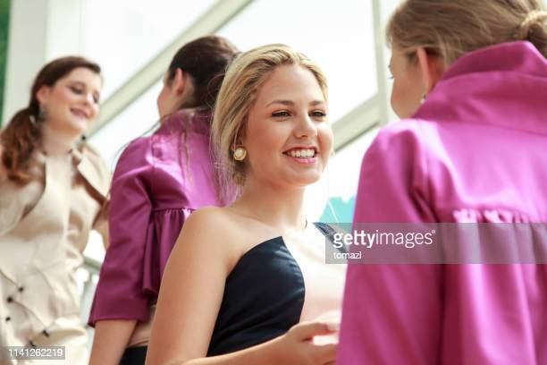 four young women talking in fashionable dresses - prom dress stock pictures, royalty-free photos & images
