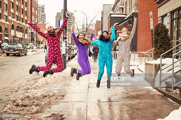 Four young women wearing onesies jumping in a winter street.