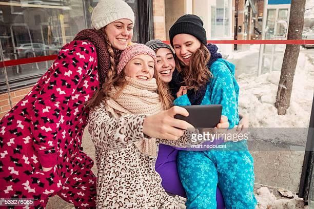 """quatro mulheres jovens usando onesies tirando uma selfie no inverno. - """"martine doucet"""" or martinedoucet - fotografias e filmes do acervo"""