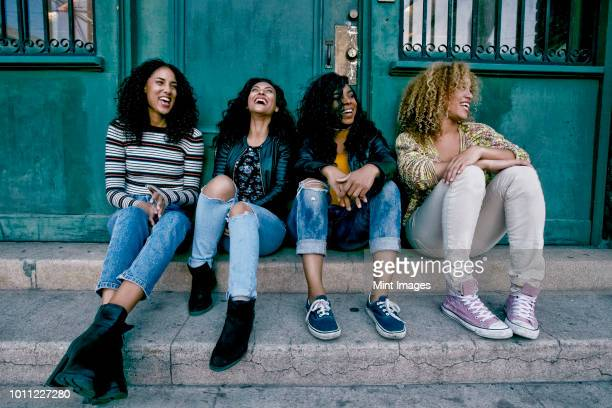 four young women with curly hair sitting side by side on steps outside a building. - female friendship stock pictures, royalty-free photos & images