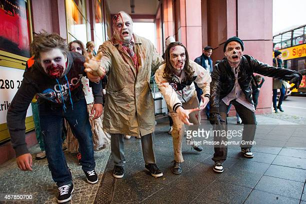 Four zombie enthusiasts walk over the Alexanderplatz as part of a flashmob on October 25 2014 in Berlin Germany Over 150 participants dressed as...