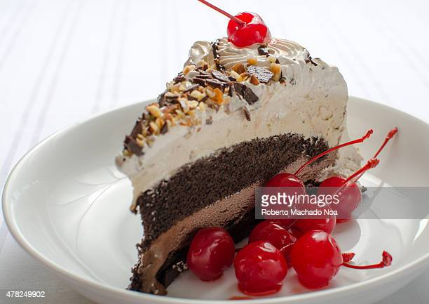A fourlayer cake and ice cream dessert topped with cherries tempts the viewer