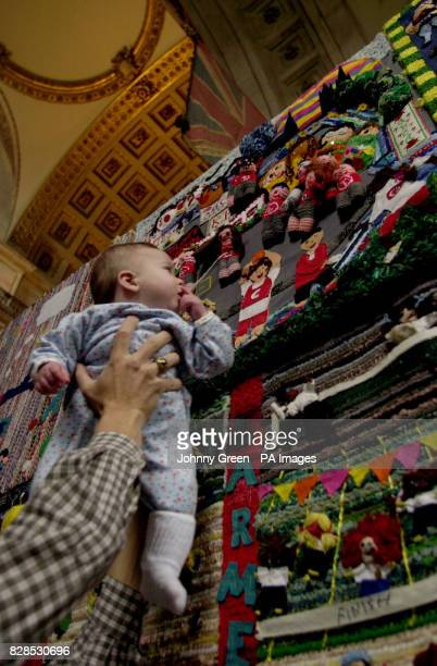 Fourmonthold Lauren Besch from Maryland in the United States of America is held aloft by her father to look at a tapestry crafted by children from...