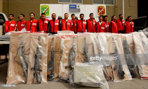 "Fourteen alleged members of ""Los Zetas"" drug cartel and seized weapons are presented to the press in Monterrey, Nuevo Leon state, Mexico on February..."