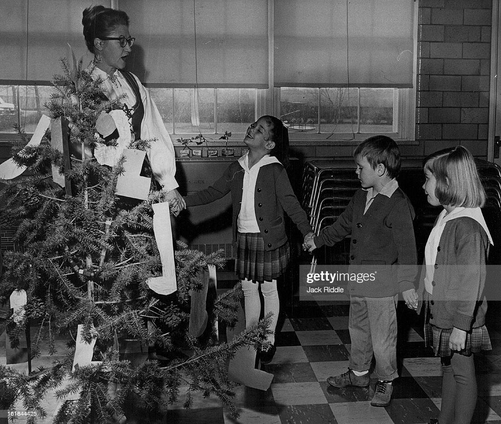 DEC 21 1964, DEC 30 1964; Fourteen Days of Christmas; The fourteen days of Christmas observance, a custom of Norway, is featured in the St. Mary's Academy holiday observance at the school at 4545 S. University Blvd. Mrs. Kathryn Murray (left) of 2754 S. P : News Photo